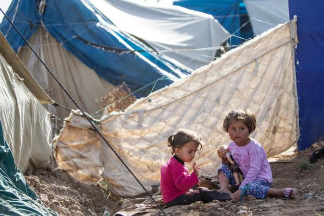 Iraq, May 2013. Two Syrian girls plays behind the tent in the Domiz refugee camp in Northern Iraq. The area is strewn with rubbish and often raw sewage but children have nowhere else to go to play. Domiz is situated near the city of Dohuk, about forty miles from the Syrian border. Approximately 40,000 Syrians are living here, in facilities provided for around half that number. April 2013 marked one year since Domiz camp opened in Dohuk, Northern Iraq. In that time it has grown to a tent city of nearly 40,000 Syrian refugees. UNICEF provides services in education, child protection, water, sanitation and hygiene, and health and nutrition. UK Nat Com local copies of these files at \Unicef-mediaphotosCOUNTRIESsyriaSY2013-refugees-IRAQ